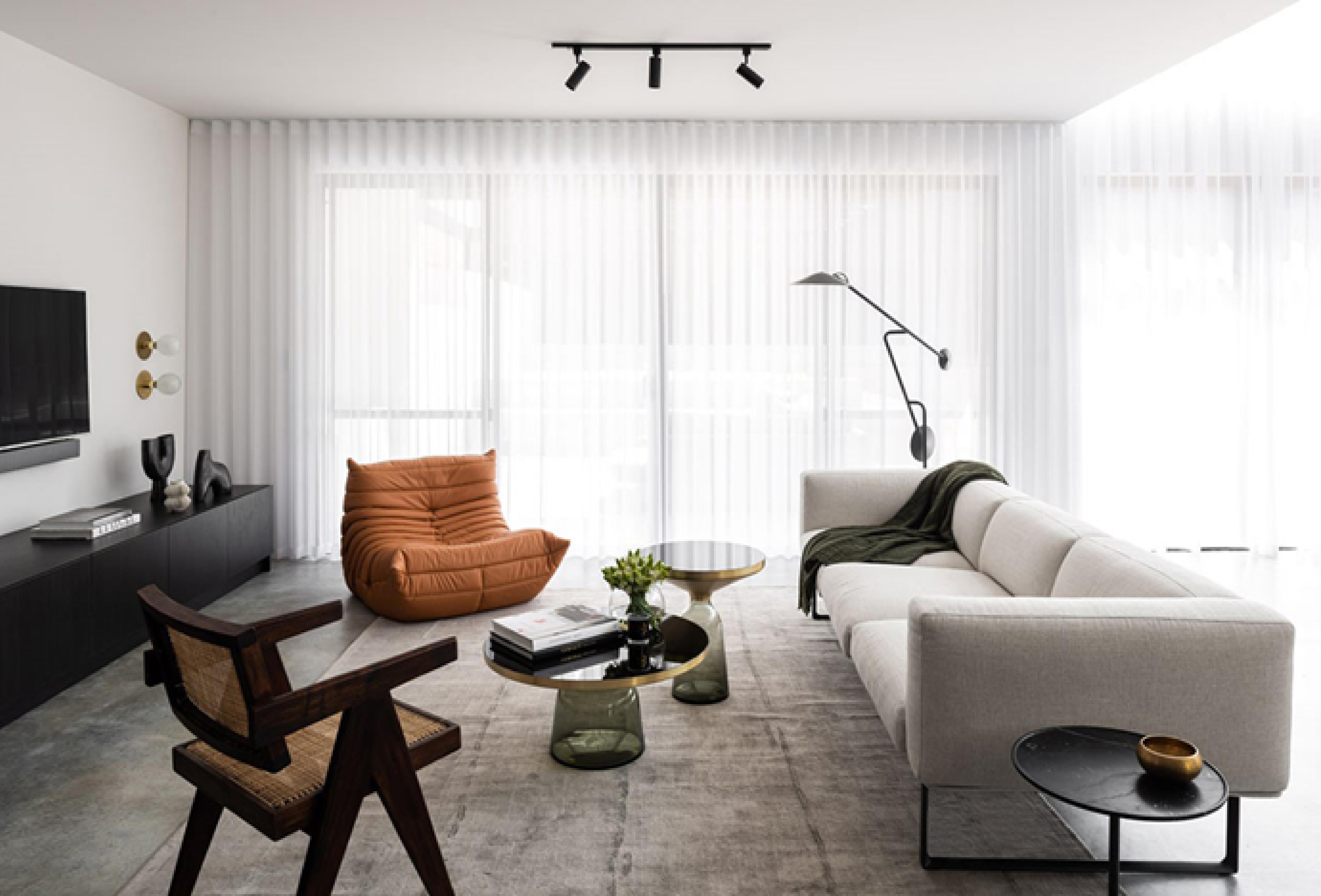 Việc sử dụng gam màu trung tính cho toàn bộ phòng khách, kết hợp chiếc ghế màu cam ngói là điểm nhấn cho phòng khách